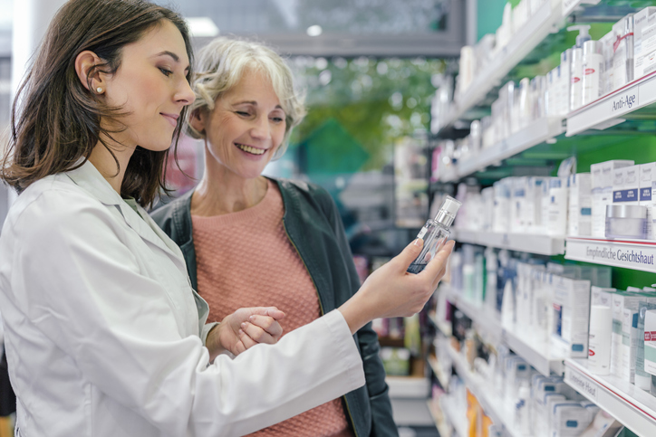 Pharmacist and another woman looking at medications on the pharmacy's shelf