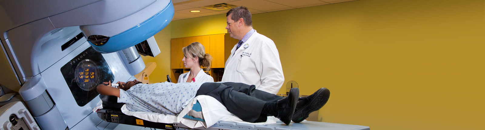 Man being scanned by advanced medical imaging device with two Ascension healthcare providers